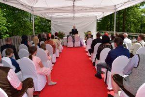 Hochzeitsgäste und das Brautpaar von hinten fotografiert